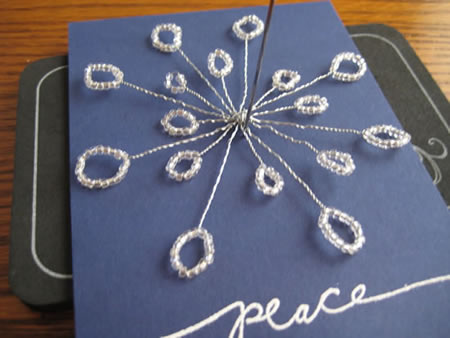 Gluing the bead snowflake that was crafted by twisting onto the cardstock card.