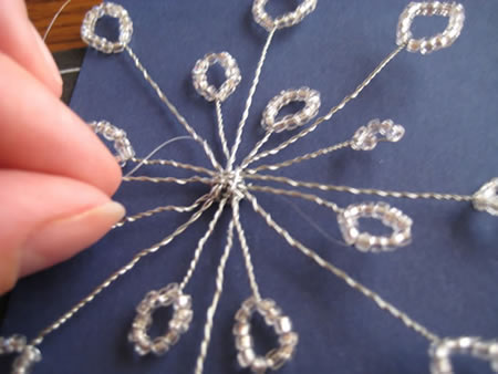 Threading the extra length of the snow flake through the cardstock for this beading craft.